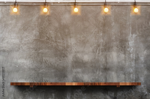 Mur Empty brown wood plank board shelf at grunge concrete wall with light bulb string party background,Mock up for display or montage of product or design