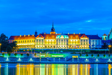 The royal castle and the old town of warsaw reflected on the Vistula river during night, Poland.