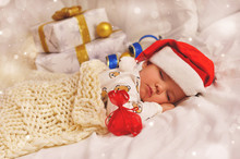 Little Baby Boy Sleeping In Pajamas And Santa Hat With A Gift In A Red Bag On The Background Of Gift Boxes