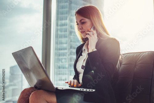 Young woman waiting in a hall sitting in modern office working on laptop talking Wallpaper Mural