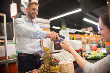 Portrait Of Happy Young Man Handing Credit Card To Smiling Cashier Paying Via Bank Terminal At Grocery Store