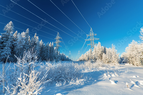 Obraz The overhead electric line over blue sky.  Electrical wires of power line or electrical transmission line covered by snow in the winter forest. - fototapety do salonu
