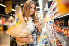 Waist Up Portrait Of Pretty Young Woman Using Smartphone And Holding Bag With Groceries While  Choosing Food In Supermarket