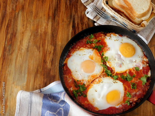 Foto op Plexiglas Gebakken Eieren A pan of fried eggs with tomato sauce and parsley on a wooden background. Shakshuka a traditional meal of the Jewish cuisine