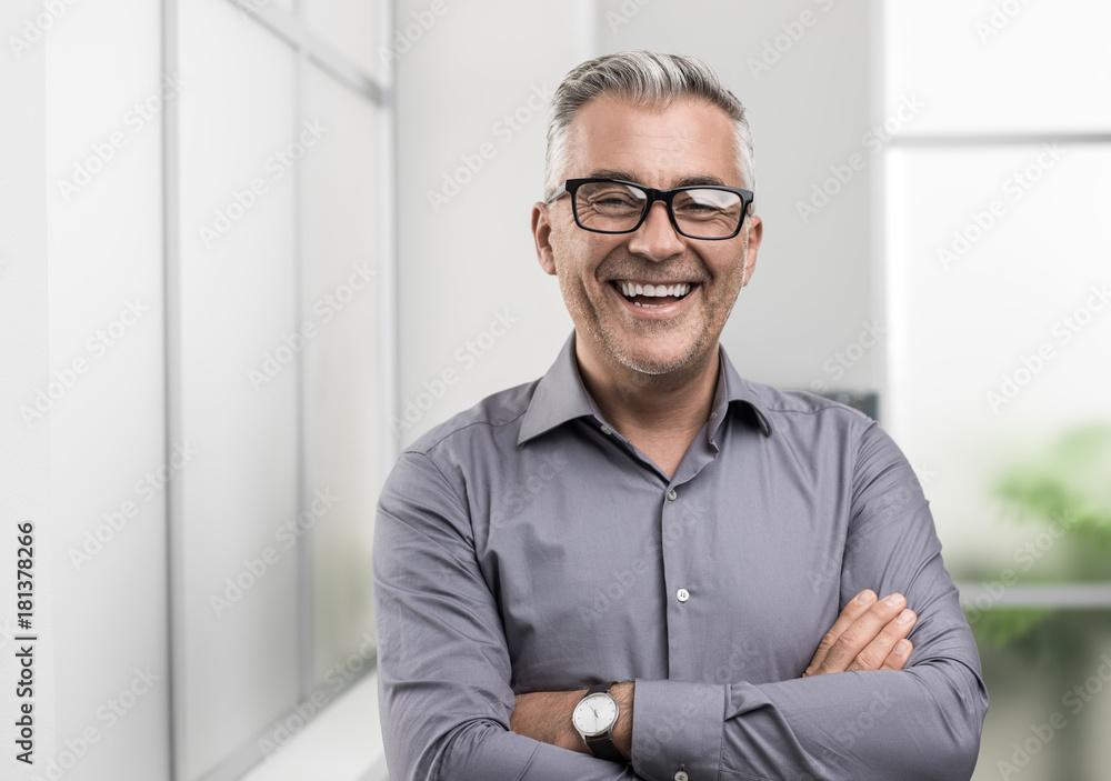 Fototapeta Confident businessman posing in the office