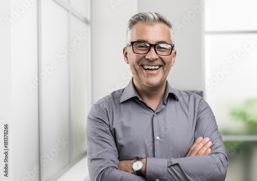 Foto Confident businessman posing in the office