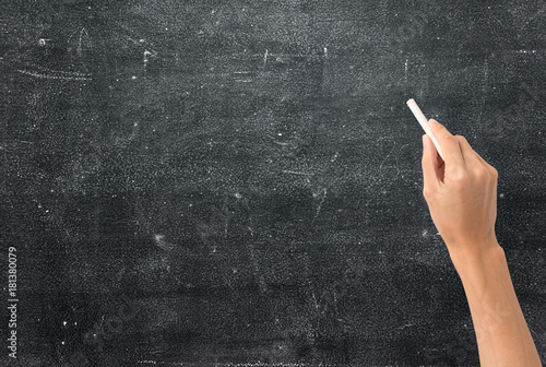 hand holding white chalk and starting to write on blank chalkboard