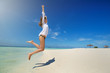 Young slim woman jumping on beach under deep blue sky. Summer vacation concept