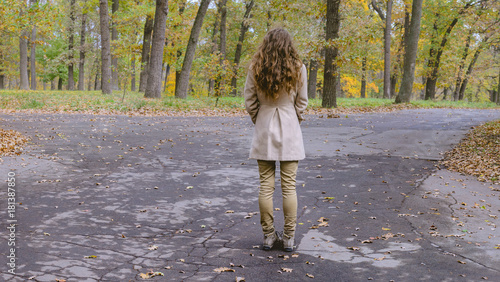 Young woman has decision at the crossroad through autumn colorful forest Wallpaper Mural