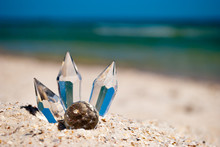 Beautiful Transparent Glass Crystals On Yellow Sand Summer Beach Sea Shore Blue Sky Vacation Rest Weekend