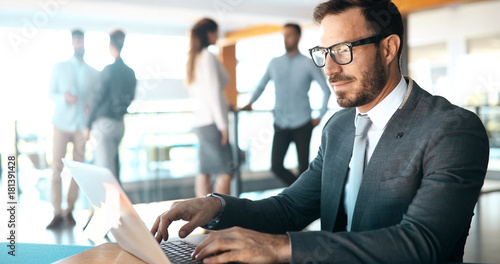 Photo  Professional businessman working on laptop in office
