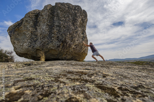 Man pushing a big stone Canvas Print