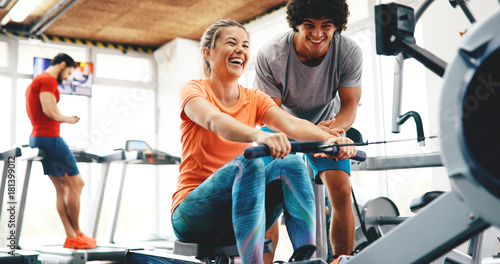 Wallpaper Mural Young beautiful woman doing exercises with personal trainer
