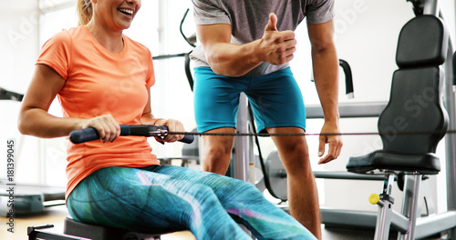 Tablou Canvas Young beautiful woman doing exercises with personal trainer