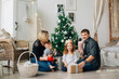 Young happy family of four having fun near christmas tree. Happy new year concept. Cheerful parents and kids