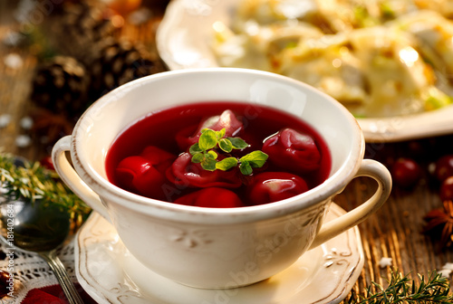 Borscht with small dumplings with mushroom filling, christmas beetroot soup in a ceramic bowl on a wooden table.  Traditional Christmas eve dish in Poland.
