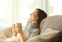Woman Relaxing At Home Holding A Coffee Mug