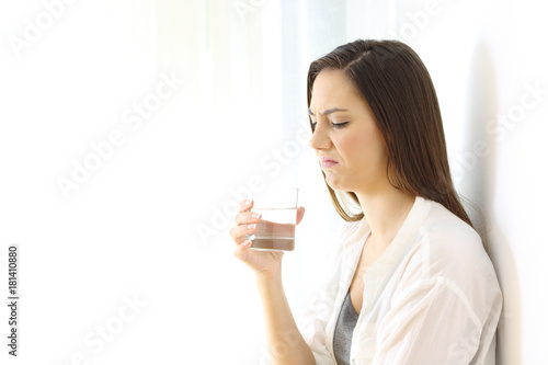 Disgusted woman drinking water with bad taste on white