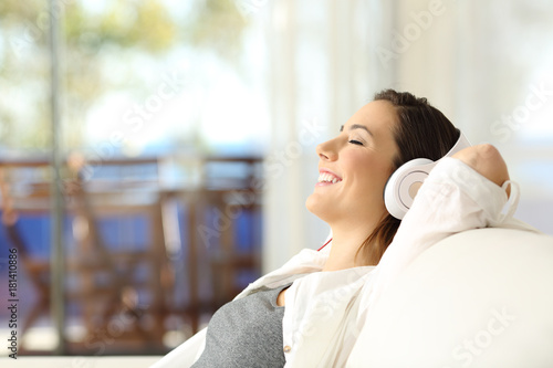Deurstickers Ontspanning Happy girl relaxing listening to music on a sofa