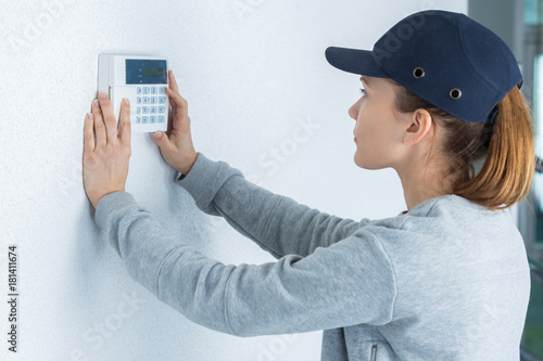 Photo  female technician pressing button on digital thermostat