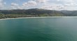 Panorama of Apollo bay town on Great Ocean road in Victoria as seen from open sea – enclosed beach coast harbour to hill ranges.