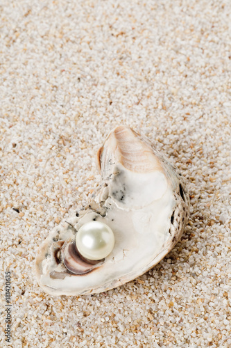 Single pearl in oyster sea shell on sand