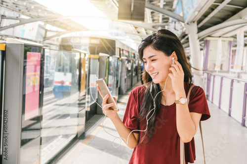 Fototapeta  Asian woman passenger with casual suit using and listening the song via smart mo
