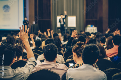 Photo Speaker on the stage with Rear view of Audience in the conference hall or semina