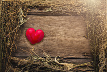 Abstract Holiday Frame With Rose Petals And Dried Flowers Leaf On Old Wooden Texture Background With Red Heart Object In The Middle
