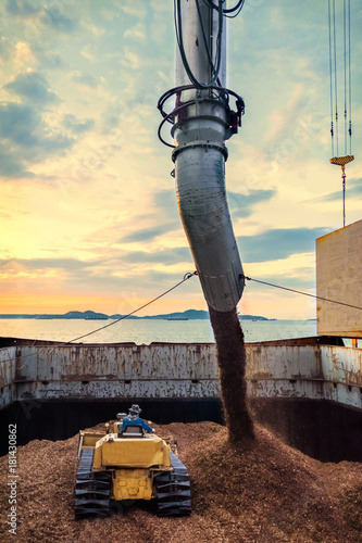 Fotografia, Obraz  bulldozers pushing bulk wood chips loading into a large vessel by a conveyor, vertical view
