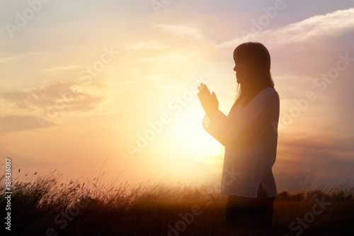Canvas Print - Woman praying and practicing yoga on nature sunset background, hope concept