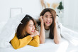 Top view of beautiful young asian women lesbian happy couple showing surprise and looking at camera while lying in bed under blanket. Funny women after wake up. Lesbian couple together indoors concept
