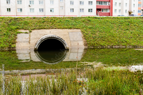Valokuva  Concrete culvert pipe hole system draining sewage water near the puddle