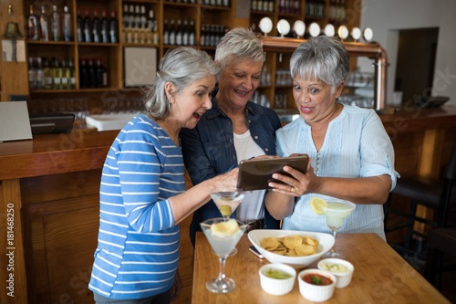 Fotografia  Senior female friends using digital tablet while having drinks