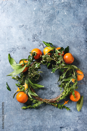 Tuinposter Olijfboom Christmas wreath with clementines tangerines and green branches over blue texture background. Top view, copy space. New Year cards and decorations.