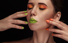 Bright Colorful Makeup In Vivid Colors On Young Attractive Womens Face. Beauty, Portrait With Orange Eyeshadows And Green Lips. Sensual Posing With Hands. Cosmetics, Healthy Skin.