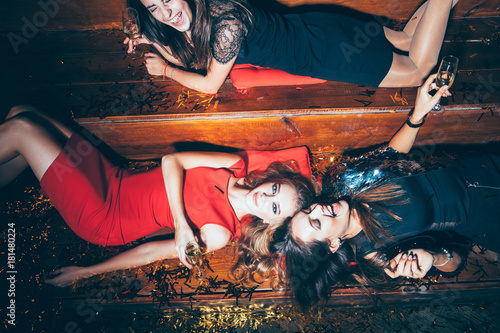 Fotografía Beautiful young women having fun on crazy party lying on the floor