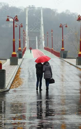 Fototapeta Couple walking under red umbrella on a rainy foggy day on the downtown Kyiv pedestrian city bridge, back view obraz na płótnie