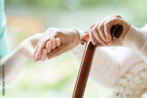 Foto  Elder person supported on stick