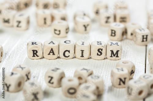Racism word written on wood block. Canvas Print
