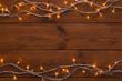 Christmas lights border on wood background