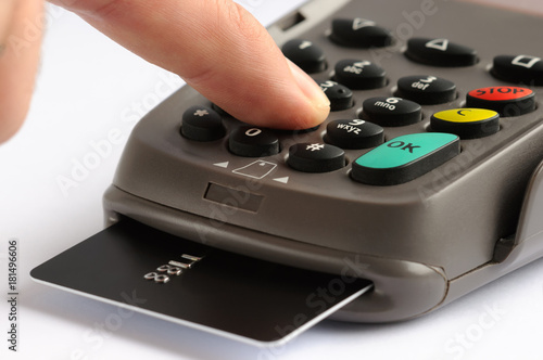 POS terminal with credit card. Man entering security code in payment terminal device with chip card inserted