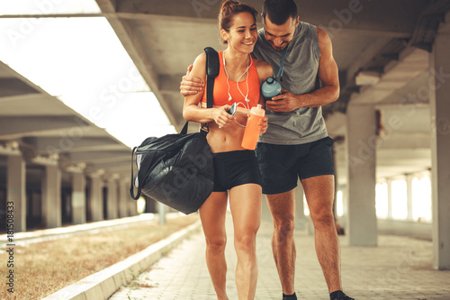 Fotografia  Young couple walking on street in sports wear.They going to gym.
