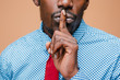 Black businessman calls on the silent, isolated on brown background