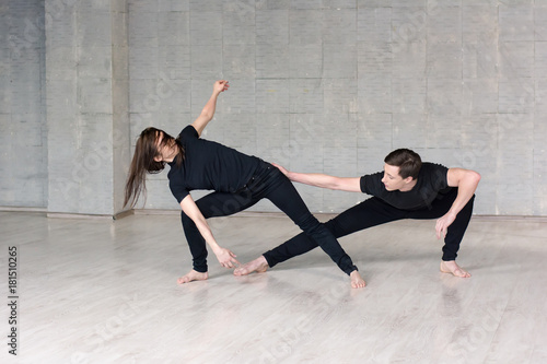 Young couple practising dance skills. Modern style young couple dancing contemporary dance on studio background.
