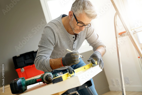 Fotografie, Tablou Man at home assembling DIY furniture