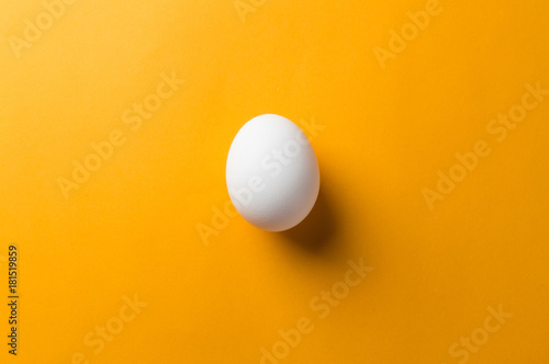 White egg and egg yolk on the yellow background. topview Fotobehang