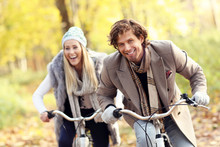 Happy Couple On Bikes In Forest During Fall Time