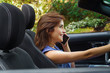 Close up of beautiful young woman using her cellphone inside of the black car, while driving her car with one hand, in a blurred nature background