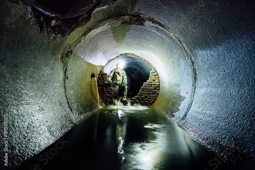 Papiers peints Canal Sewer tunnel worker in special chemical protective suite in underground sewer tunnel examining sewage collector